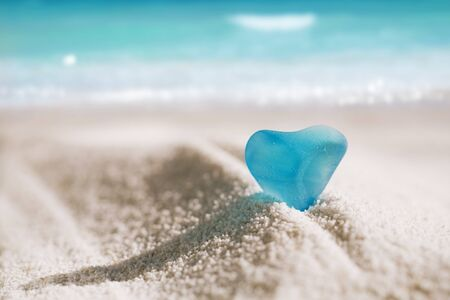 sea glass blue heart on white sand beach with seascape