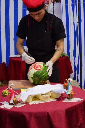 carves: Man carves rose on watermelon