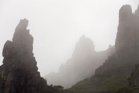impregnable: Rocks in the fog on the peninsula Kony. Magadan Region. The Sea of Okhotsk. Russia.