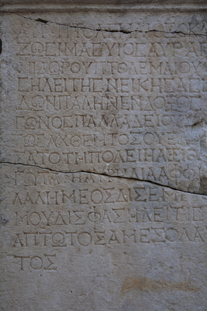 greek alphabet: Ancient Greek writing on a limestone slab. The ancient city of Phaselis. Turkey.
