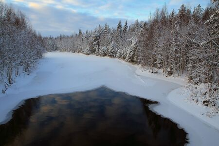 thawed: Thawed patch on ice river in the forest. Winter Karelia. Russia.