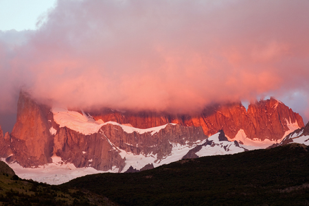 vertex: The red light on the mountain in the cloud. Mount Fitz Roy. Patagonia. Argentina.
