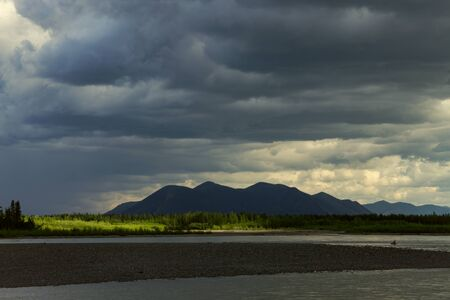 cloudiness: The spot of light on the dark side of the river. Indigirka River. Yakutia. Russia.
