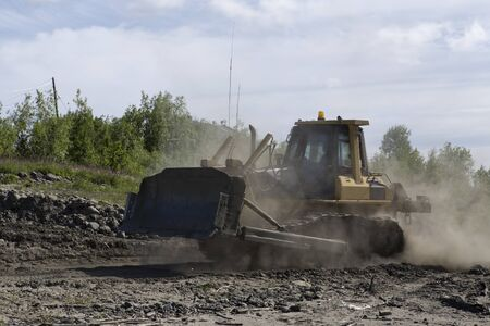 Bulldozer in motion and dust. The shore of the Lena River. Yakutia. Russia.