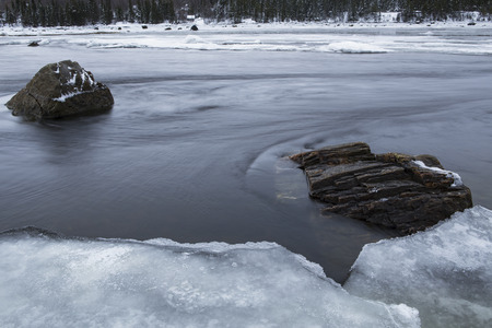flux: Two stones in the river and the ice coast. White Sea. Murmansk region. Russia.