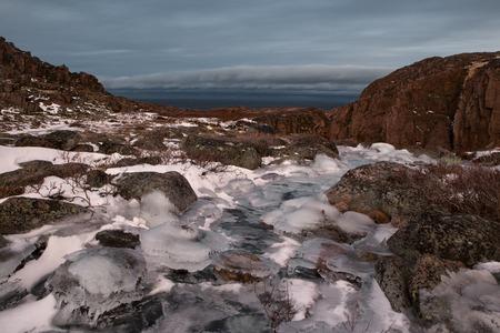 frozen creek: The frozen creek in the rocks on the background of the sea. Murmansk region. Kola Peninsula. Russia. Stock Photo