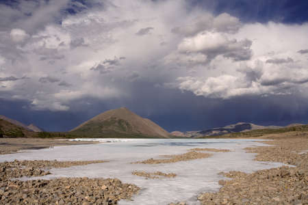 alarming: Remains of ice in the valley of the mountain river and beautiful clouds. Ridge Suntar-Hayata. Yakutia. Russia.