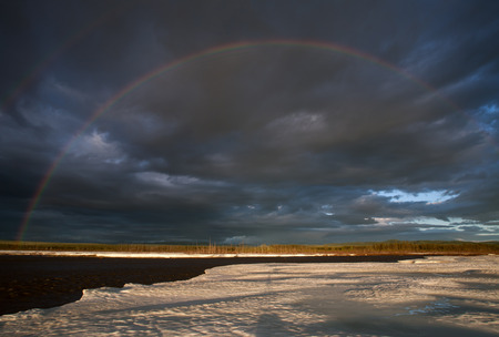 emphatic: Remains of the ice on the river and rainbow. Moma River. Yakutia. Russia.