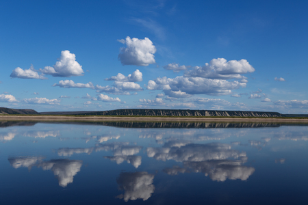 buoyant: Reflection of clouds in the river and the distant shore. Lena river. Yakutia. Russia.