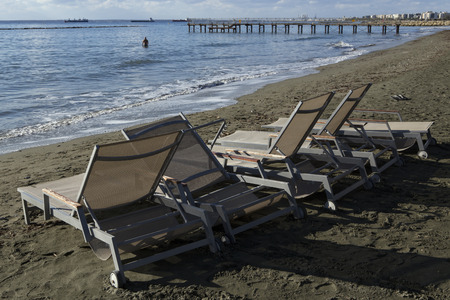 bather: Sunbeds on the beach and a man in the sea. Cyprus. Limassol.
