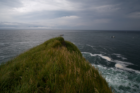 morose: Grassy cliff above the sea. The boat in the sea
