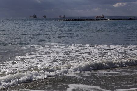 seafront: The seashore and the ships in the distance. Limassols seafront promenade. Cyprus.