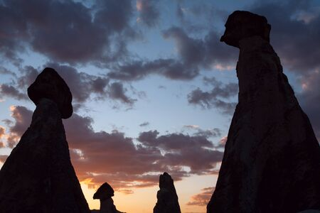 head stones: Rock silhouettes against the backdrop of the sunset sky. Cappadocia. Turkey.