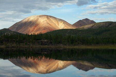 stillness: Beautiful mountain and its reflection on the calm lake water. Oimyakon Highlands. Yakutia. Russia.