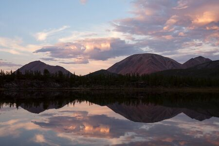 quietness: Beautiful mountain and its reflection on the calm lake water. Oimyakon Highlands. Yakutia. Russia.