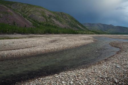 fluorescence: mountain; river; stony; way; rock; glow; luminescence; fluorescence; dull; gray; murky; grey Stock Photo