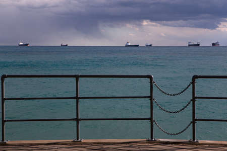 seafront: Wooden pier on the beach. Ships at sea. Limassols seafront promenade. Cyprus. Stock Photo