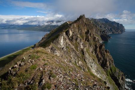 abrupt: The narrow rocky ridge and the sea on both sides. Peninsula Kony. The Sea of Okhotsk. Magadan Region. Russia.