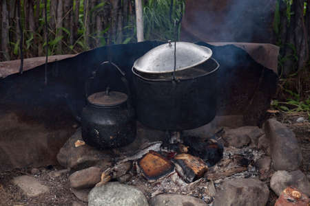 Pots and steaming kettle on the hearth. Traditional way of life of the Yakut horse breeders.