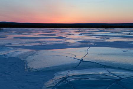 cracks in ice: Ice field in cracks and red sky. Indigirka. Yakutia. Russia. Stock Photo