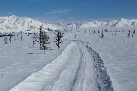 recessive: Winter road in the snowy mountains. Moma Mountains. Yakutia. Russia. Stock Photo