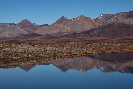 lifeless: Lifeless mountains with a reflection in the lake. Ridge Cherskiy. Yakutia. Russia. Stock Photo