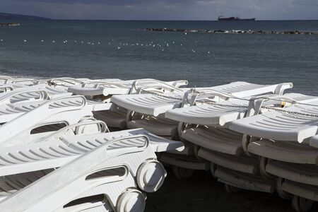 lounges: A stack of beach lounges out of season. Limassols seafront promenade. Cyprus.