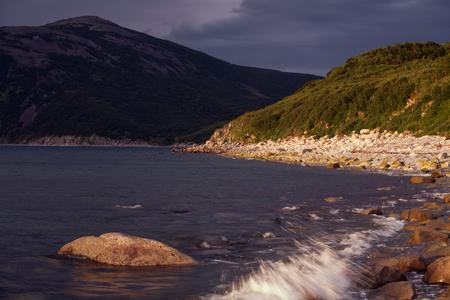 sputter: Sea bay surrounded by mountains. Peninsula Kony. The Sea of Okhotsk. Magadan Region. Russia. Stock Photo