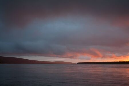 roomy: The sky over the big river in the sunset light. Lena river. Yakutia. Russia.