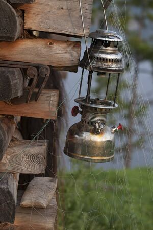 fishing cabin: Old kerosene lamp on the wooden frame and the fishing net. Lena river. Yakutia. Russia. Stock Photo