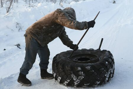 breakage: Man reconditioning wheel of the car in the winter. Yakutia, Russia.
