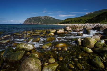 The creek flows into the sea. Koni Peninsula, Magadan region, The Sea of Okhotsk, Russia.