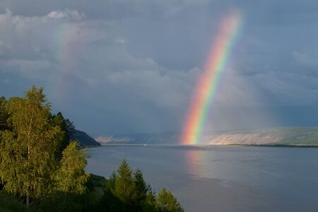 ample: The bright rainbow over the big river. Lena river. Yakutia. Russia. Stock Photo