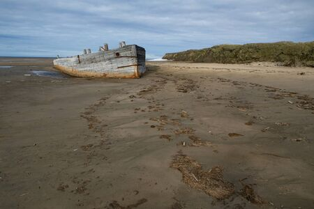 unhappiness: Old wooden ship stranded on a sandy beach. Laptev sea. Yakutia. Russia. Stock Photo