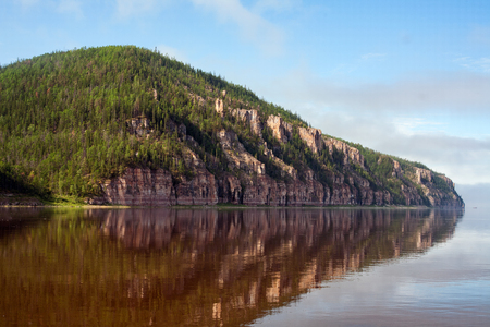 lena: Rocky river bank and its reflection on the water. Lena river. Yakutia. Russia.