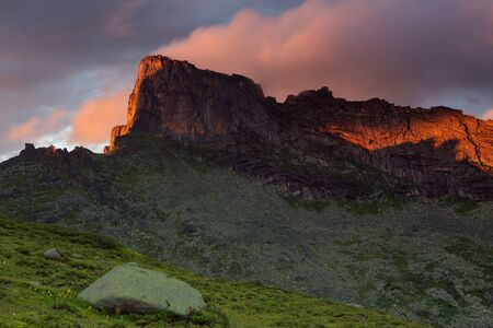 Rocky peak in the red light of the setting sun. Natural Park Ergaki. Western Sayan. Russia.