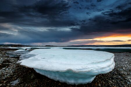 Ice formation on the river. Cloudy and sunset time. Moma River. Yakutia. Russia.