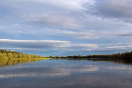 The coastline to the wood between the sky and the river. Indigirka River. Yakutia. Russia.
