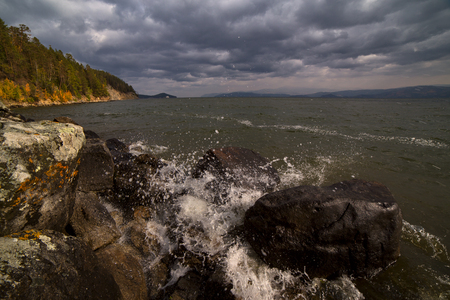 Spray from the waves on the rocky shore of the lake. Lake Baikal. Chivyrkuisky Bay. Russia.