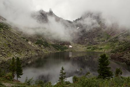 Mountain lake in the fog. Western Sayan. Natural Park Ergaki. Krasnoyarsk region. Russia.