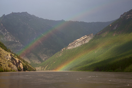 Double rainbow above the muddy river in the mountains. The River Indigirka. The Republic Of Sakha. Russia. Stock Photo