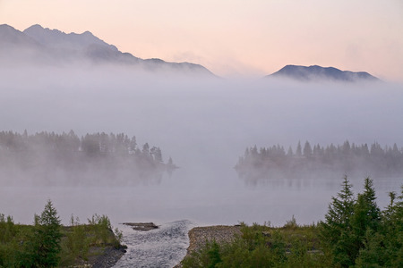 semitransparent: Morning fog over a mountain lake. Lake Dabir. Yakutia. Russia.