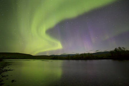 Aurora Borealis over the river. River Paypudyna. Polar Urals. Russia.