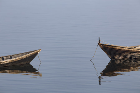 Wooden boat on the calm surface of the lake. Chivyrkuisky Bay. The Lake Baikal. Buryatia. Russia. Stock Photo
