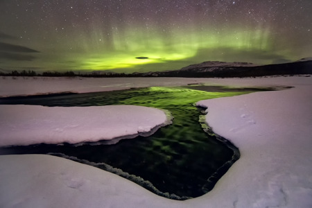 Aurora Borealis over the frozen river. The River Sob. Polar Urals. Russia. Foto de archivo