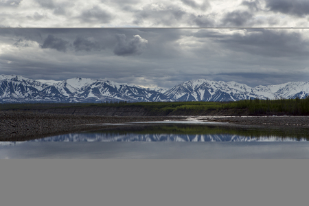 Spring mountains with remnants of snow and the reflection in the river. The River Indigirka. Yakutia.