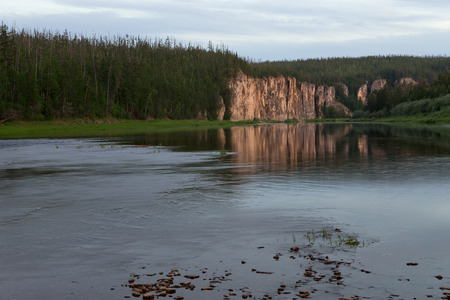Rocky coast reflected in the river. Natural Park Siine. Yakutia. Banco de Imagens - 92169911