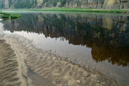 Rocky coast reflected in the river. Natural Park Siine. Yakutia.