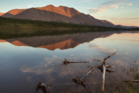 The light of the low sun on the top of the mountain. The reflection of the mountains in the lake. Yakutia. Foto de archivo