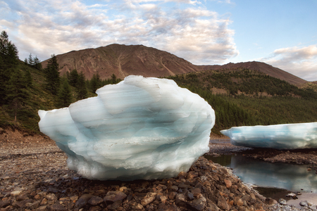 Remnants of spring ice in the valley of a mountain river. The ice field. Tomponsky district. Yakutia. Foto de archivo